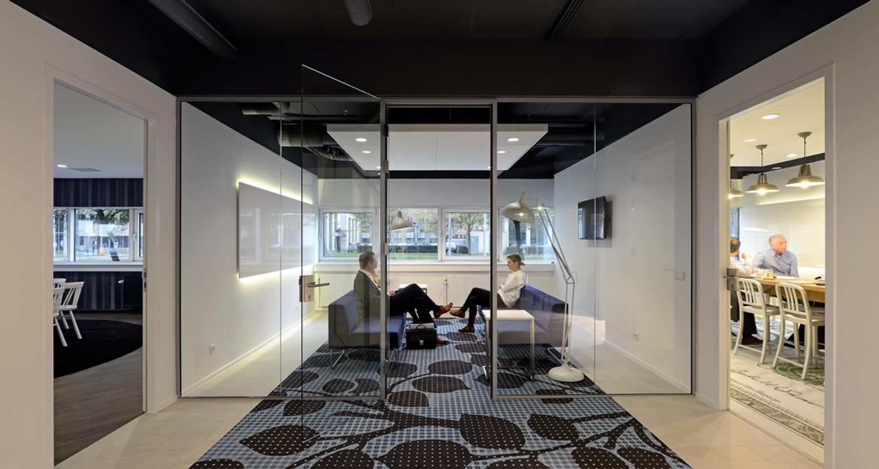 amsterdam zuidoost kantoorpand informele vergadersetting twee grijze banken twee personen vergadering