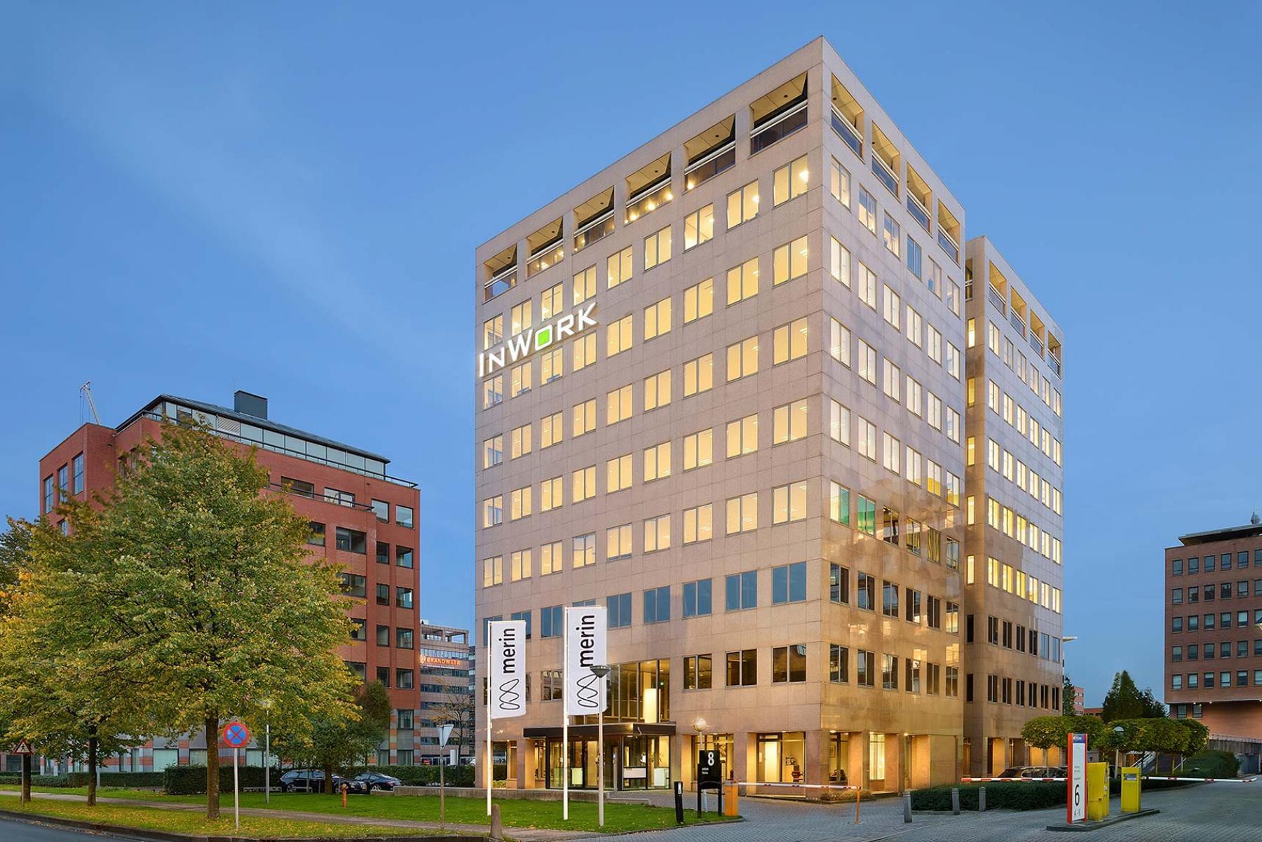 voorzijde kantoorpand amsterdam zuidoost karspeldreef vlaggen licht bomen
