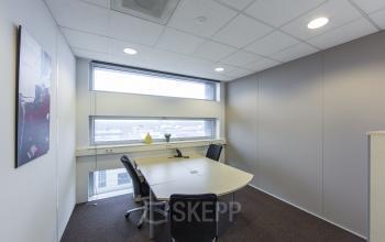 gemeubileerde kantoorkamer bureau kast stoelen vloerbedekking raam muurschildering uitzicht kantoorgebouw almere vlakbij centraal station busplein huur SKEPP