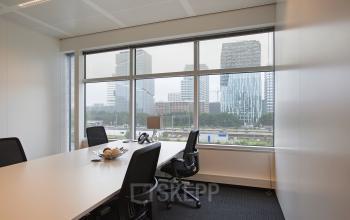 kantoorruimte amsterdam zuidas tafel bureau stoelen vloerbedekking ramen uitzicht strawinskylaan
