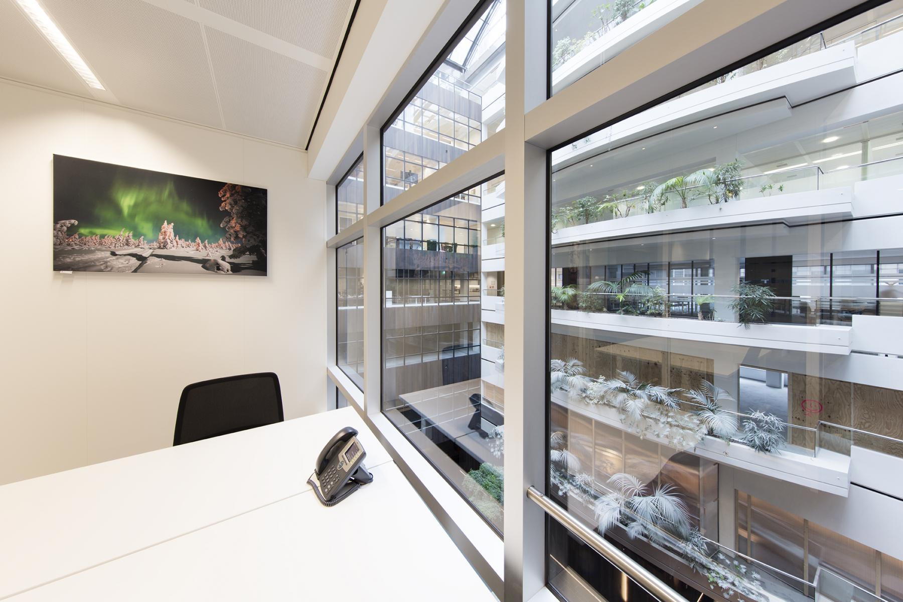 bureau bureaustoel schilderij raam uitzicht lichtinval telefoon