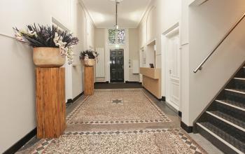 gemeenschappelijke gang met trap naar 1e verdieping en receptiebalie in kantoor in amsterdam centrum
