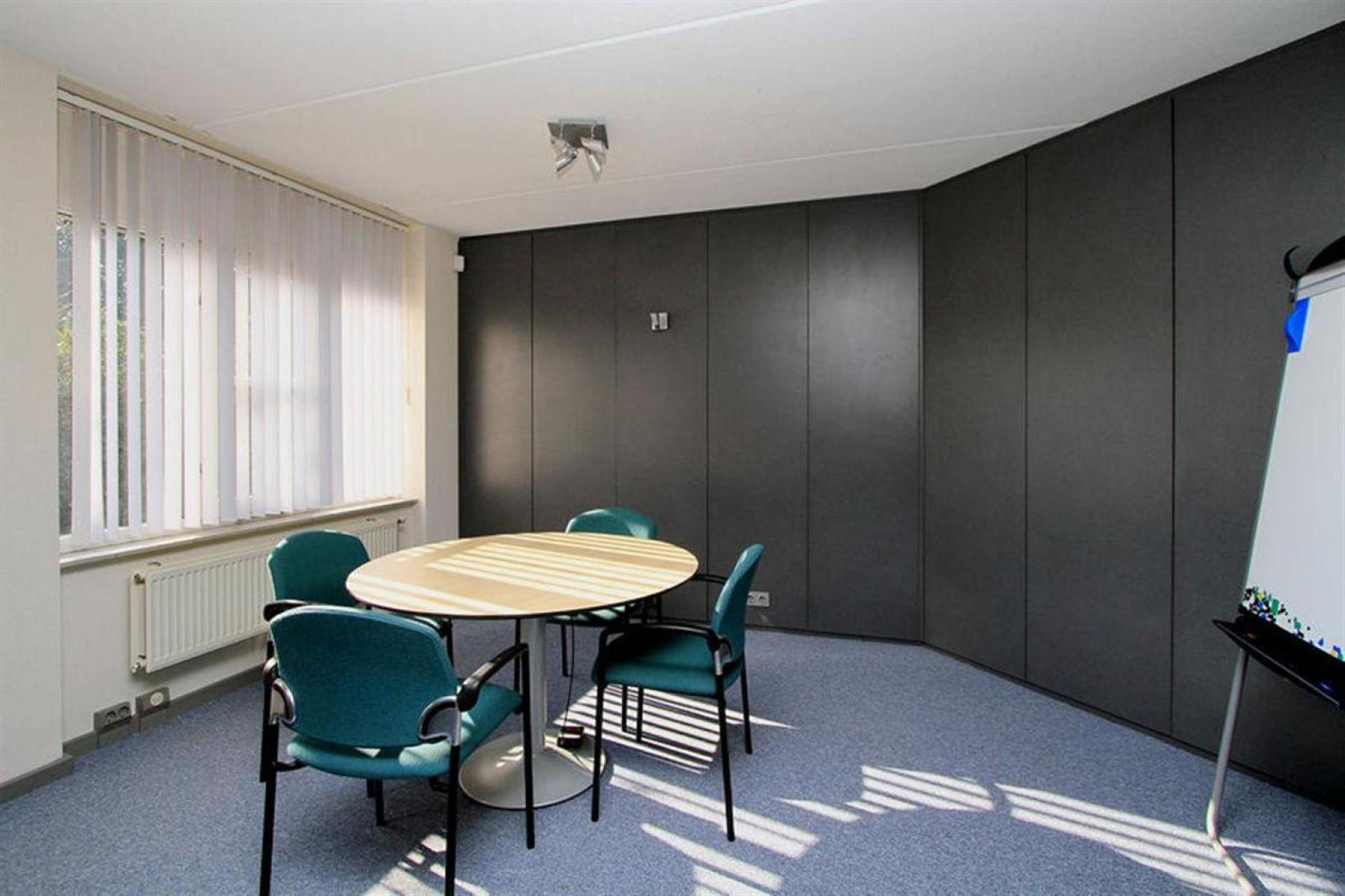 vergaderruimte presentatiemogelijkheden tafel stoelen flipover vloerbedekking ramen uitzicht muren kantoorgebouw apeldoorn