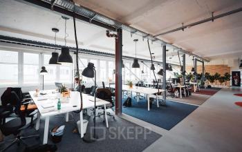 Moderner Coworking-Bereich in großem Büroraum mit viel Lichteinfall