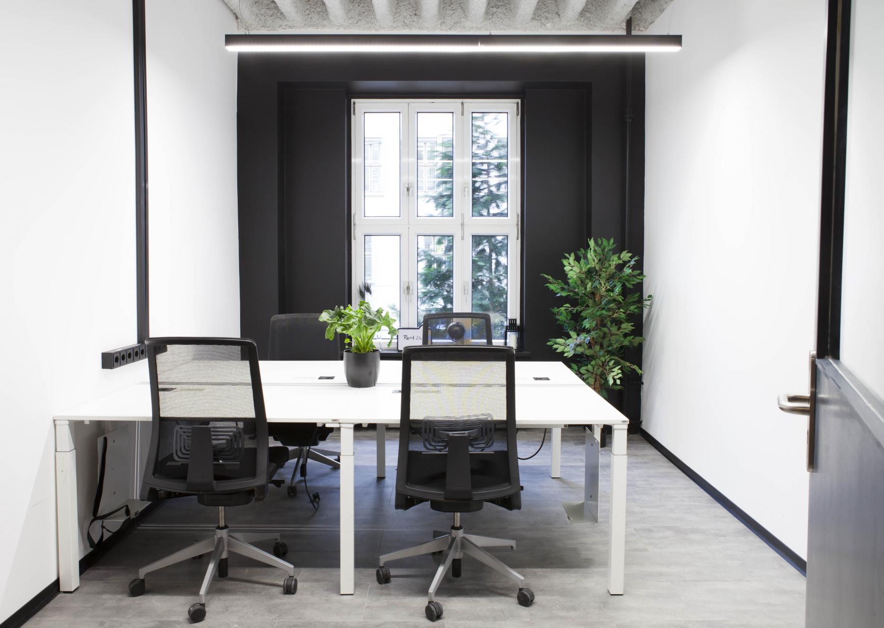 Modern eingerichtetes Büro in frischen Farben und großem Fenster