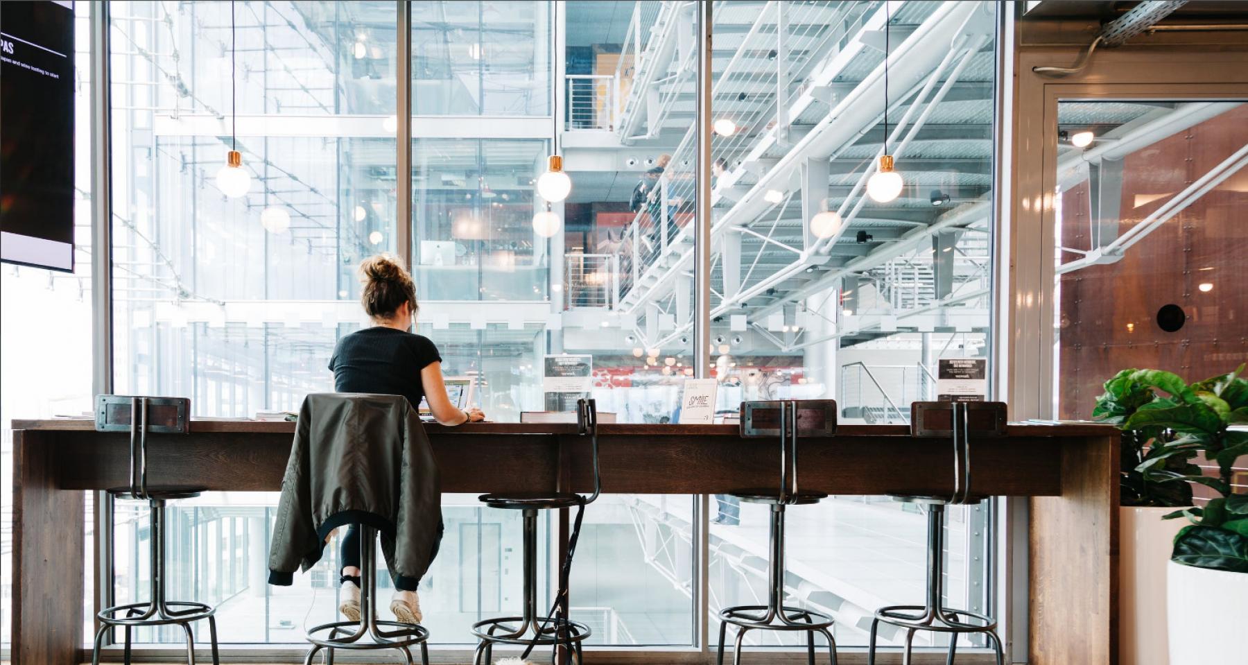 Arbeitsplatz an Glasfassade mit Blick ins Foyer