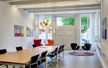 algemene ruimte lunchtafel vergaderruimte loungestoelen schilderijen deur lampen huur kantoorruimte dordrecht haven water