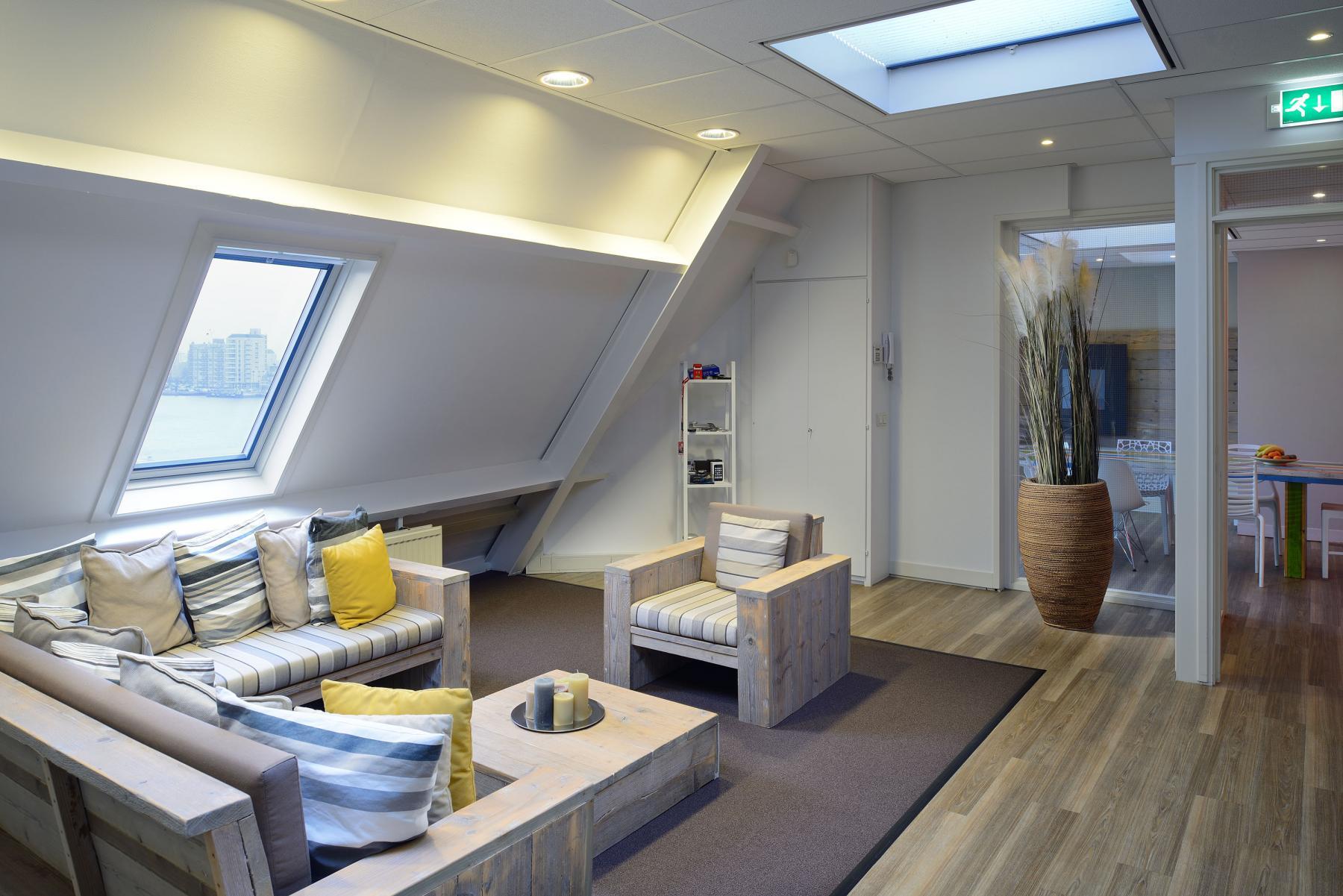 algemene ruimte kantoorpand dordrecht loungeruimte informeel overleggen banken raam uitzicht deuropening plant vloerkleed parket