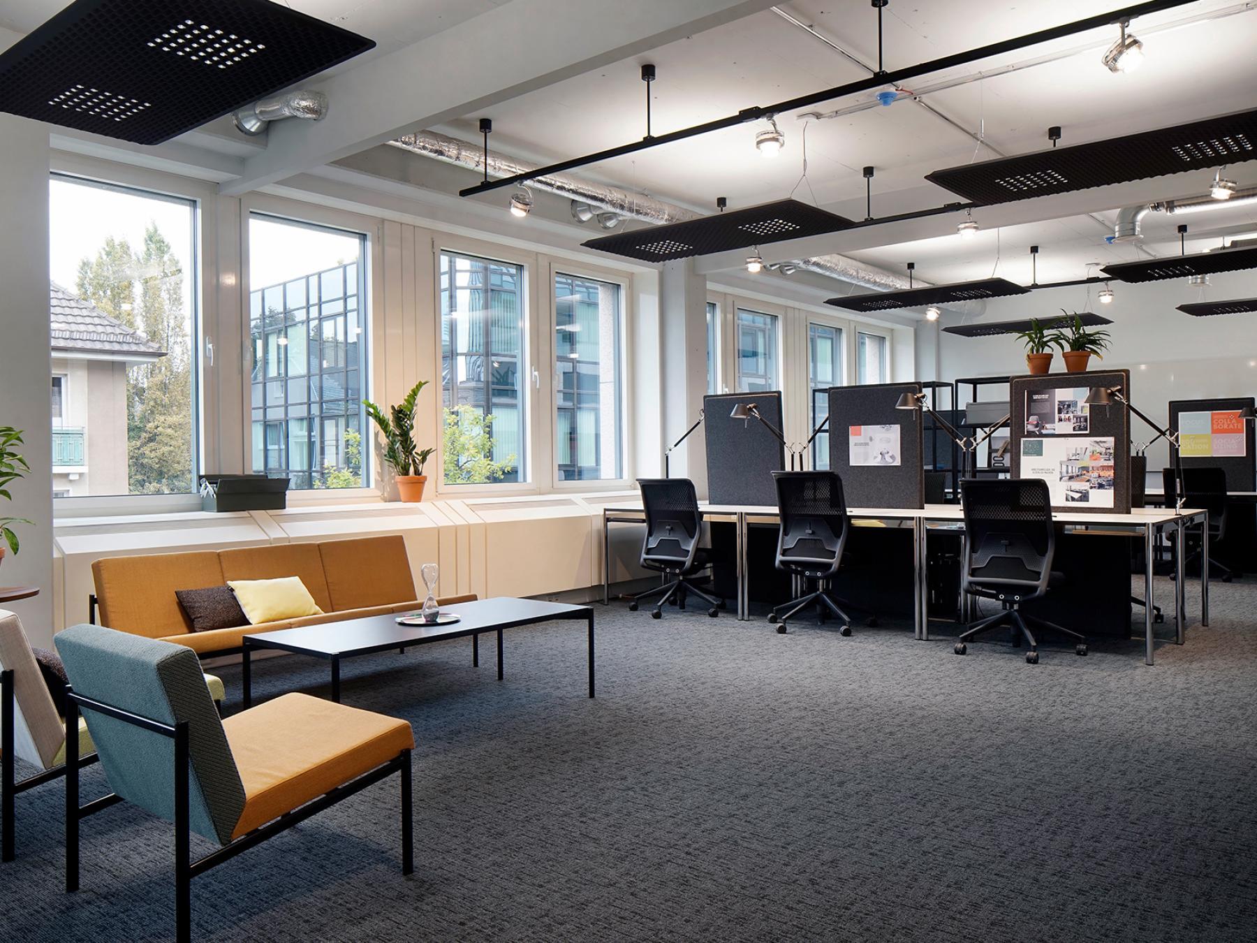 Arbeitsplätze und gemütliche Ecke in freundlichem offenen Büroraum