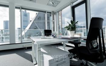 Arbeitsplatz in großem Büroraum mit Rundumverglasung