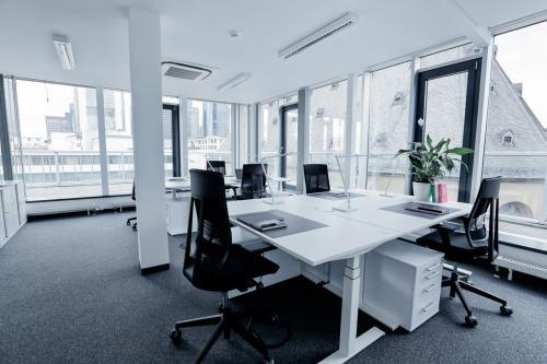 Großer Büroraum mit mehreren Arbeitsplätzen und großen Fenstern