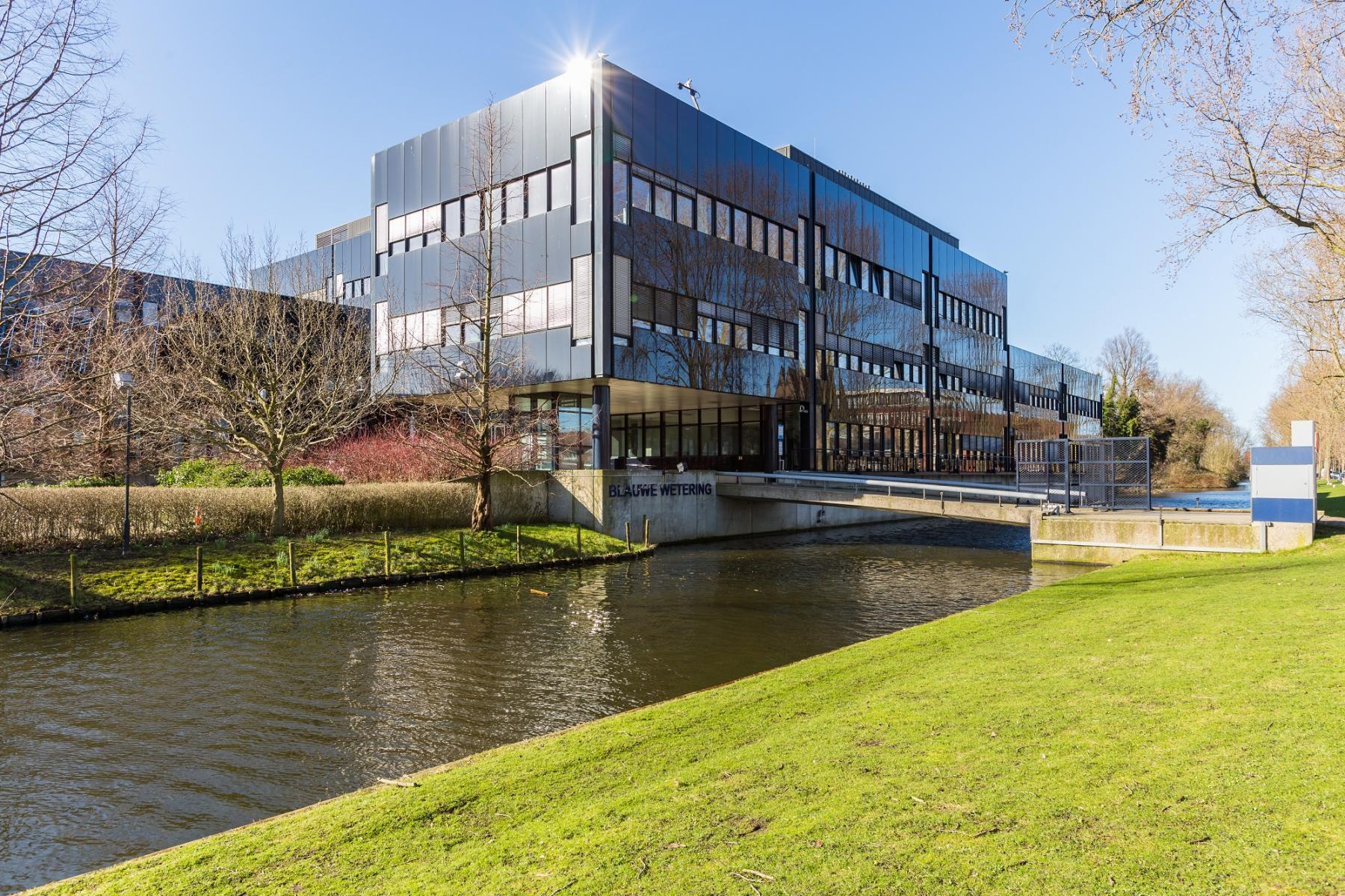 office building haarlem next to canal green environment