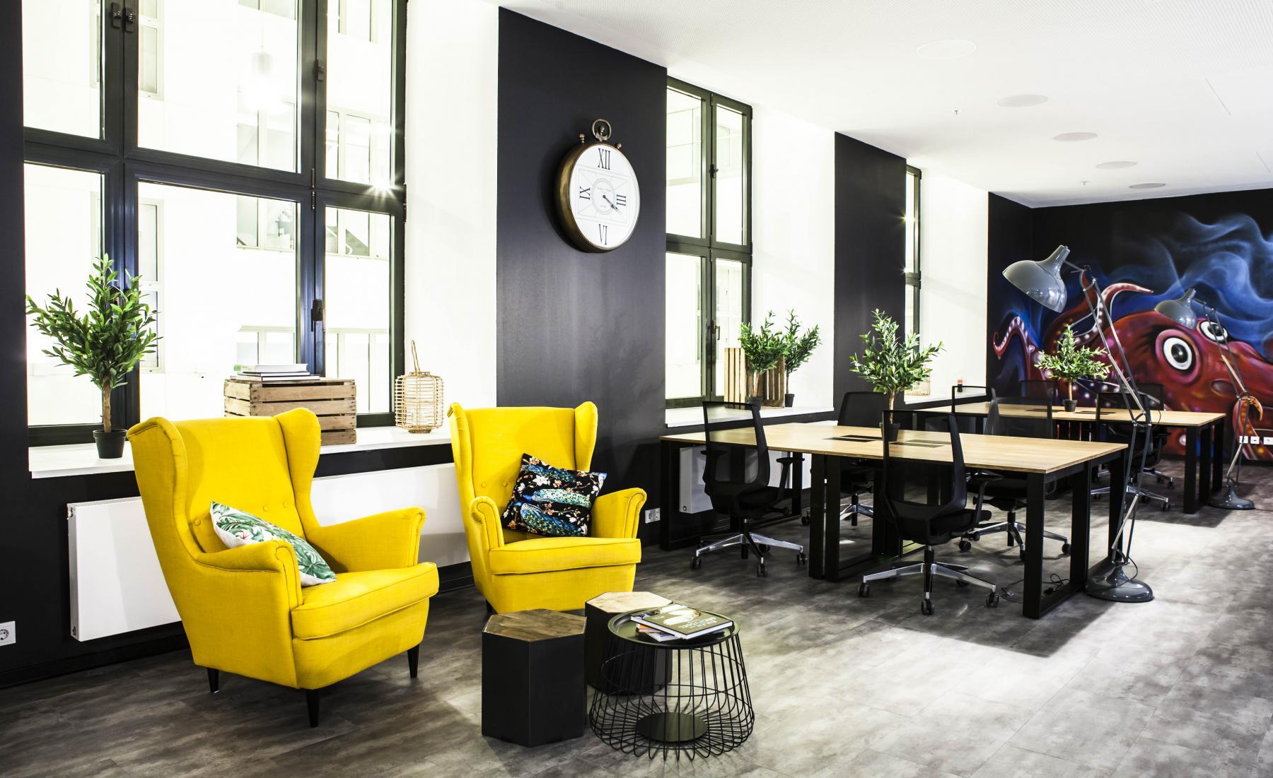 Großer Büroraum mit flexiblen Arbeitsplätzen und gelben Sesseln zum Entspannen