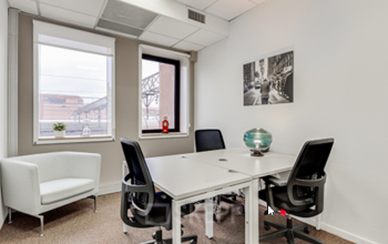 Espace de bureau partagé avec trois bureaux et un canapé confortable à la place Charles Béraudier