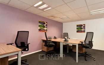 Zone de coworking chaleureuse avec des couleurs vives et des chaises confortables à l'avenue du Prado