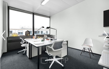 Helles Büro mit weißen Möbeln und großem Fenster