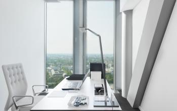 Helles Einzelbüro mit modernen Möbeln und großem Fenster