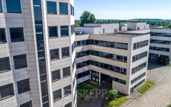 Außenansicht modernes Bürogebäude und Parkplätze für Autos