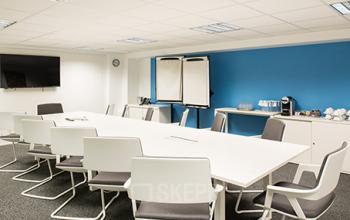 Salle de réunion lumineuse avec table et chaises blanches dans la rue Taylor