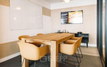 Cette salle de réunion lumineuse avec une table en bois offre une ambiance chaleureuse au boulevard Pereire