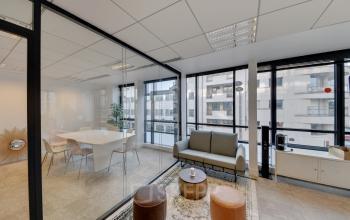 Espace de convivialité avec un canapé confortable et accès à une salle de réunion à la rue de Villiers