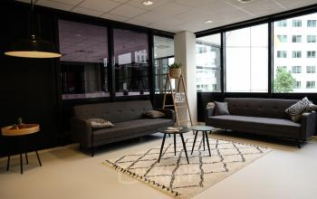 loungeruimte banken tafel stoelen ontspanning informele vergadering raam uitzicht kantoor rotterdam marten meesweg
