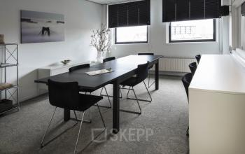 small meeting room with black tables and chairs