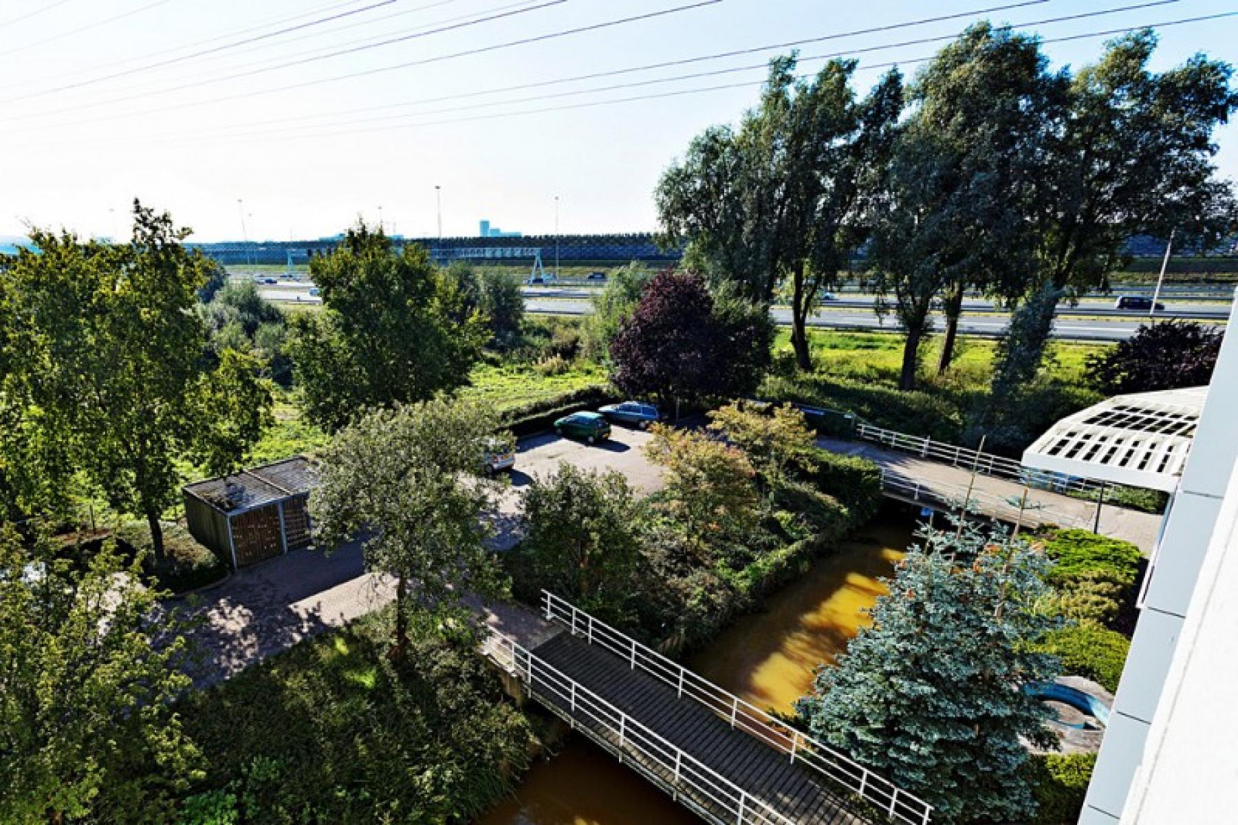uitzicht kantoorruimte parkeerplaats auto's fietsenstalling bomen groene omgeving utrecht